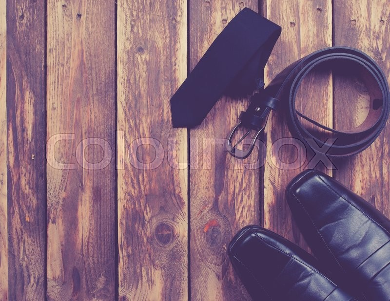 Stock image of 'Man's style accessories,tie, shoes and a belt on wooden background,vintage color toned image'
