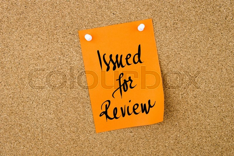 Stock image of 'Issued For Review written on orange paper note pinned on cork board with white thumbtacks, copy space available'