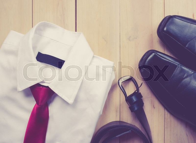 Stock image of 'Man's style accessories,shirt with a bright tie, shoes and a belt on wooden background,vintage color toned image'