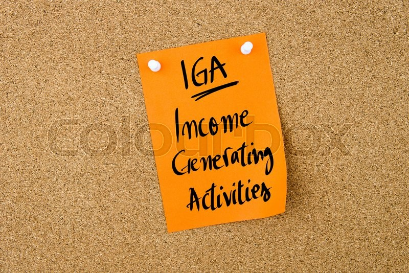 Stock image of 'Business Acronym IGA Income Generating Activities written on  yellow paper note pinned on cork board with white thumbtack, copy space available'