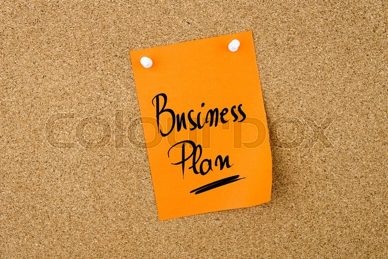 Stock image of 'Business Plan  written on orange paper note pinned on cork board with white thumbtacks, copy space available'