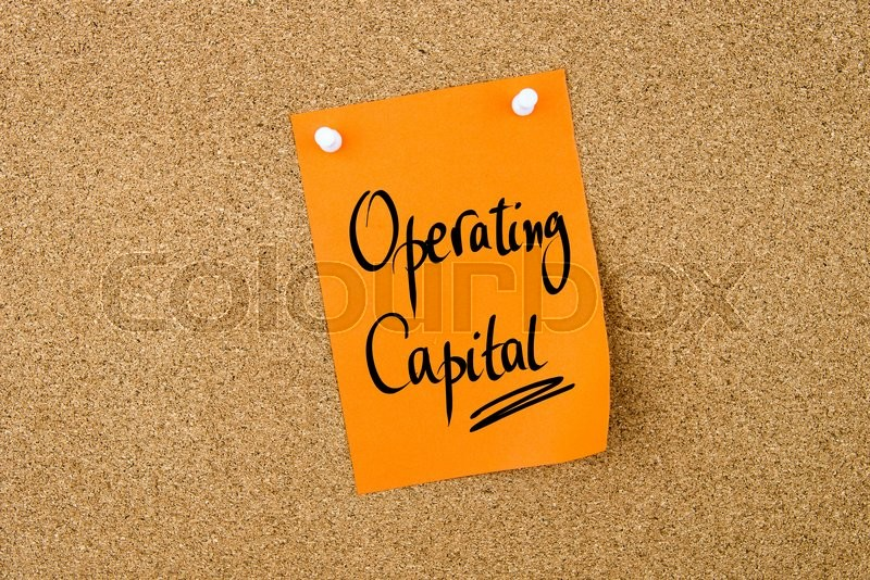 Stock image of 'Operating Capital written on orange paper note pinned on cork board with white thumbtacks, copy space available'