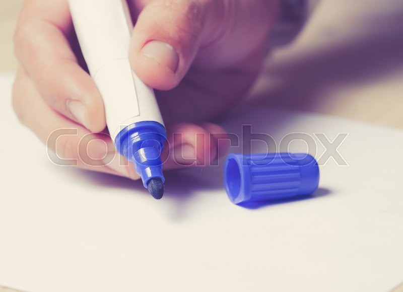 Stock image of 'Close-up of Human Hand holding pen Signing on Formal Paper at the Table'