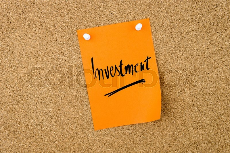 Stock image of 'Investment written on orange paper note pinned on cork board with white thumbtacks, copy space available'