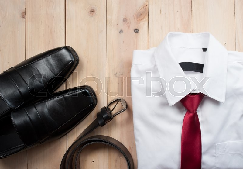 Stock image of 'Man's style accessories,shirt with a bright tie, shoes and a belt on wooden background'