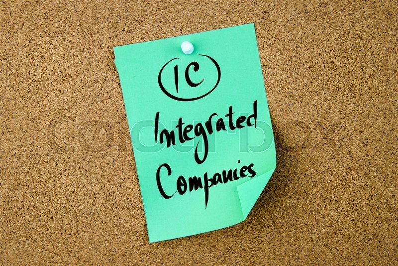 Stock image of 'Business Acronym IC Integrated Companies written on green paper note pinned on cork board with white thumbtack, copy space available'