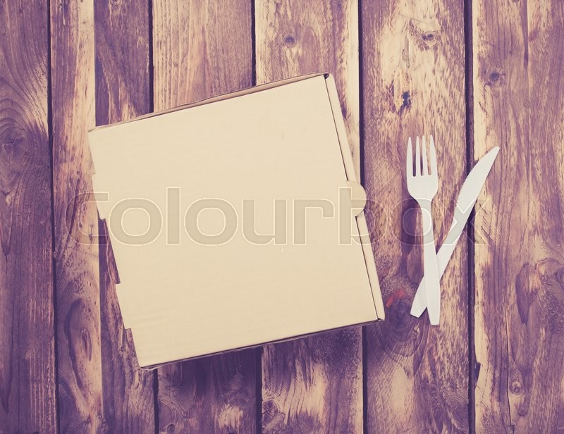 Stock image of 'Blank pizza box with Plastic knife and fork on wood background,vintage color toned image'