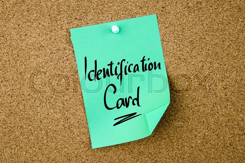 Stock image of 'Identification Card written on green paper note pinned on cork board with white thumbtacks, copy space available'
