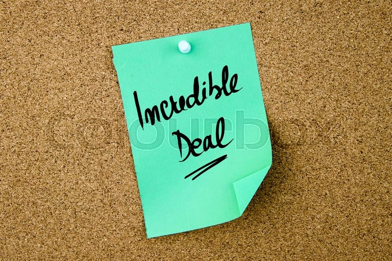Stock image of 'Incredible Deal written on green paper note pinned on cork board with white thumbtacks, copy space available'