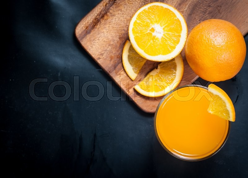 Stock image of 'Fresh fruits Orange juice in glass on on a black slate,Selective focus on glass'