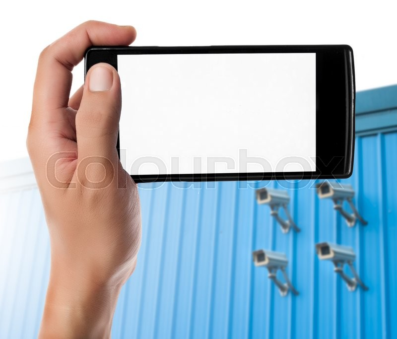 Stock image of 'Hand holding smart phone on blurred CCTV camera background. Security online concept.'