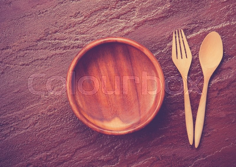 Stock image of 'Empty  bowl with fork and spoon on stone background,,vintage color toned image'