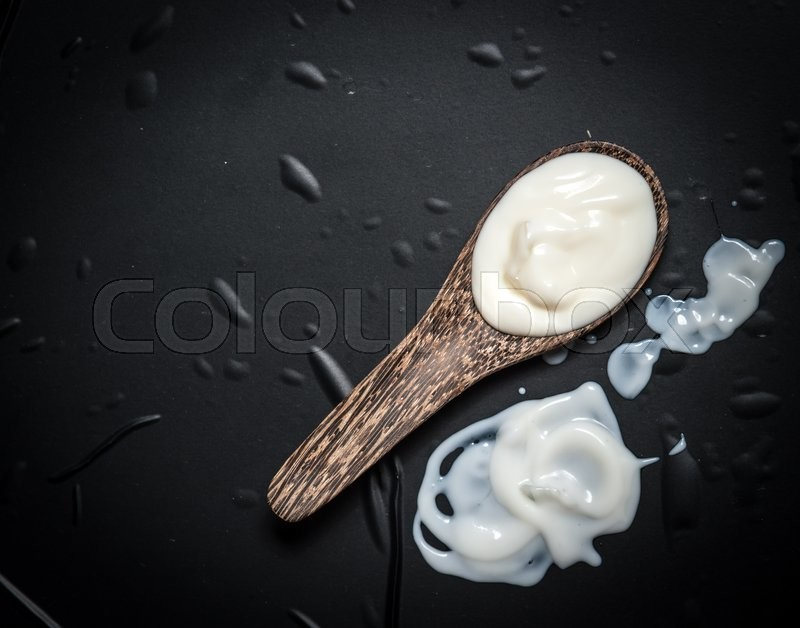Stock image of 'Wooden spoon with milk cream on a black slate'