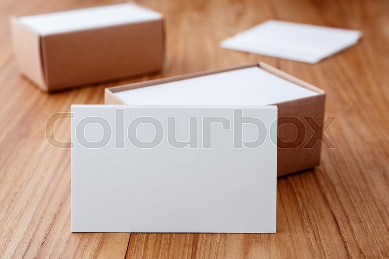 Stock image of 'Business card blank mockup with kraft box on wood desk'