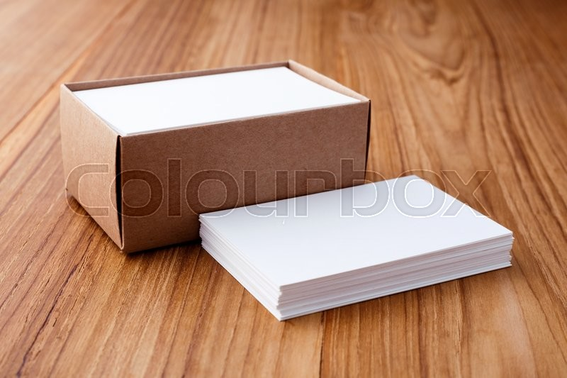 Stock image of 'Business card stack blank mockup with kraft box on wood desk'