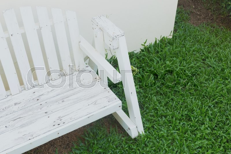 Stock image of 'white wooden bench seat in green grass garden'