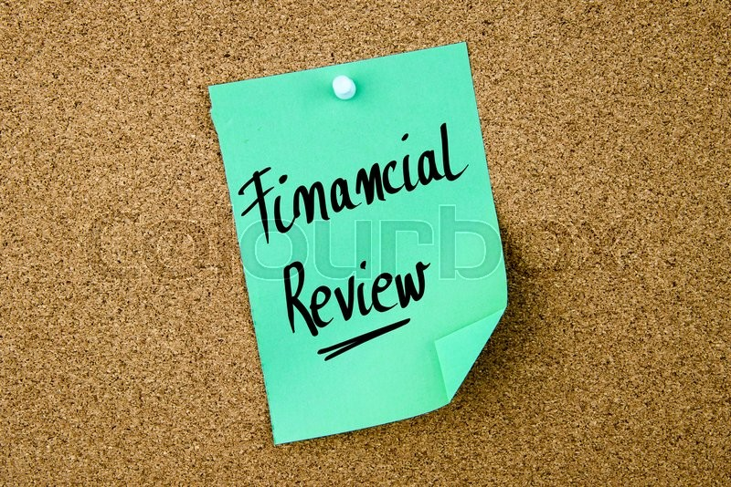 Stock image of 'Financial Review written on green paper note pinned on cork board with white thumbtacks, copy space available'
