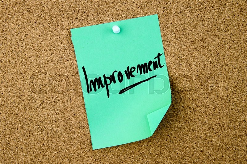 Stock image of 'Improvement written on green paper note pinned on cork board with white thumbtacks, copy space available'