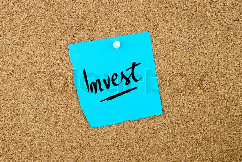 Stock image of 'Invest written on blue paper note pinned on cork board with white thumbtacks, copy space available'