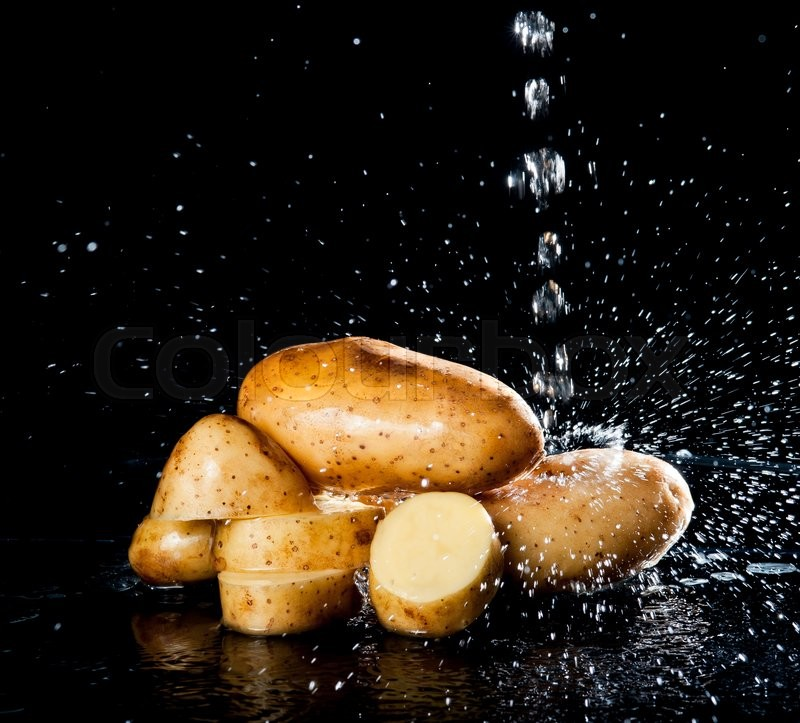 Stock image of 'Potato with water splash on black background'