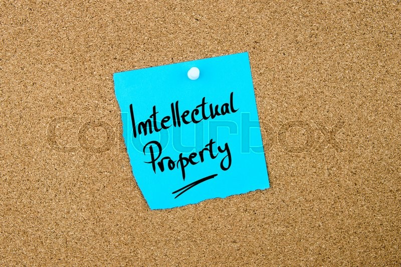 Stock image of 'Intellectual Property written on blue paper note pinned on cork board with white thumbtacks, copy space available'