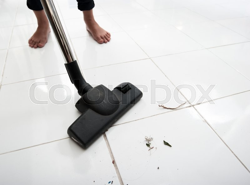 Stock image of 'Vacuum cleaning dirt on a tiled floor'