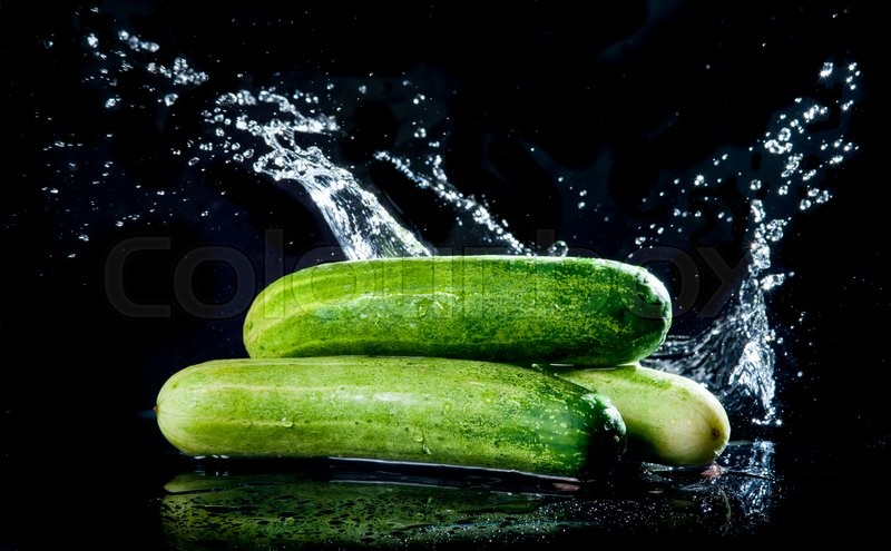 Stock image of 'Cucumber with water splash on black background'