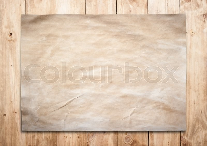 Stock image of 'Old paper on a brown wooden surface.'