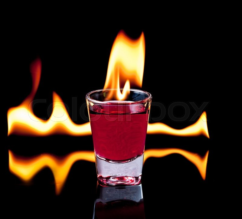 Stock image of 'Burning Red cocktail in shot glass on black background'