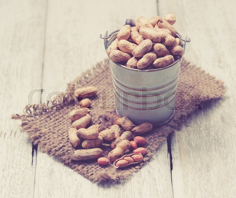 Stock image of 'Peanuts on the wooden background,vintage color toned image'