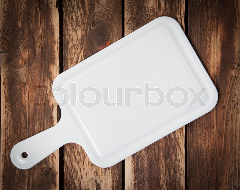 Stock image of 'White Plastic cutting board isolated on wood background.'