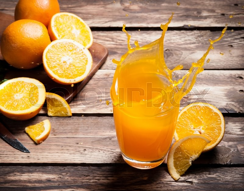 Stock image of 'Glass of splashing orange juice on wood'