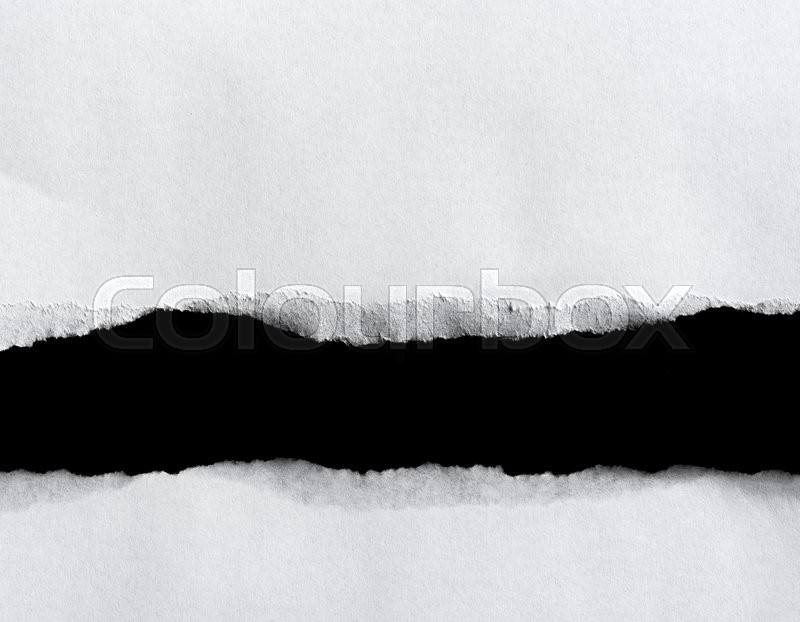 Stock image of 'White torn of paper isolated on a black background.'