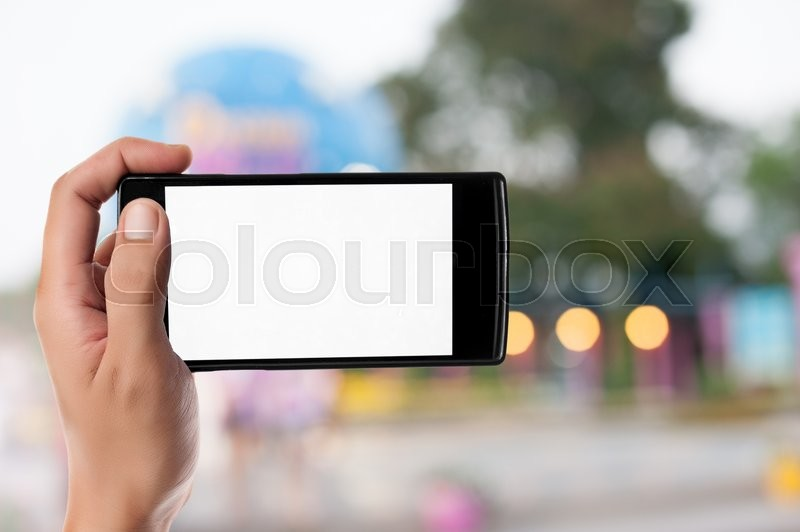 Stock image of 'Hand holding smart phone on blurred park, natural background'