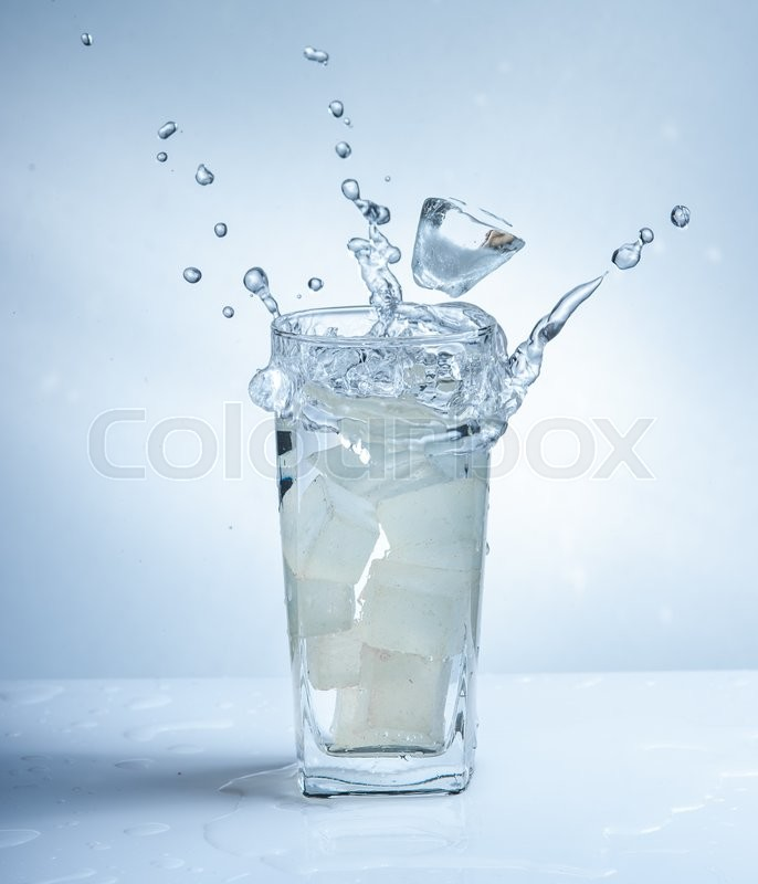 Stock image of 'Ice cubes with water splash in glasses on blue background'