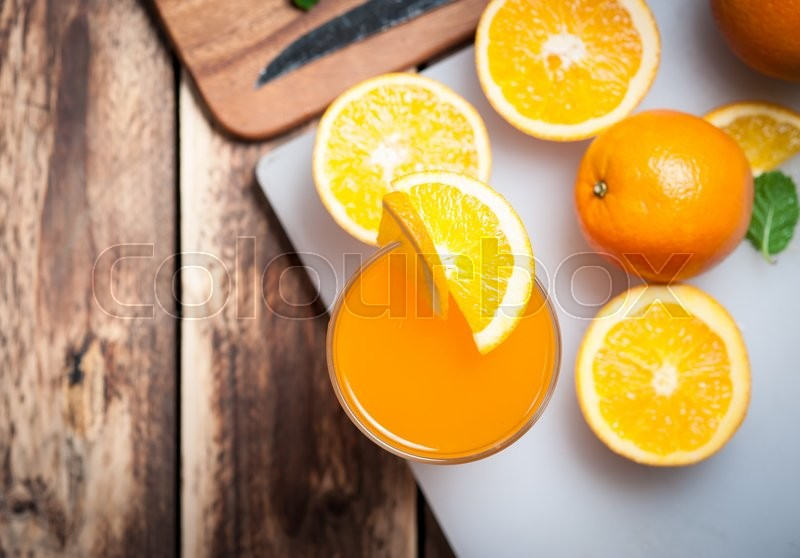 Stock image of 'Fresh fruits Orange juice in glass on wood,Selective focus on glass'