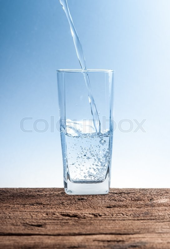 Stock image of 'Pouring water on glass on wood'