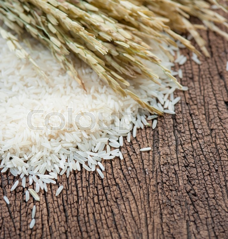 Stock image of 'White rice and paddy pile on wood background,Selective focus'