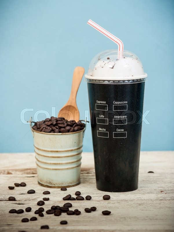 Stock image of 'Iced coffee with coffee beans on wood vintage background,Selective focus on paper cup'