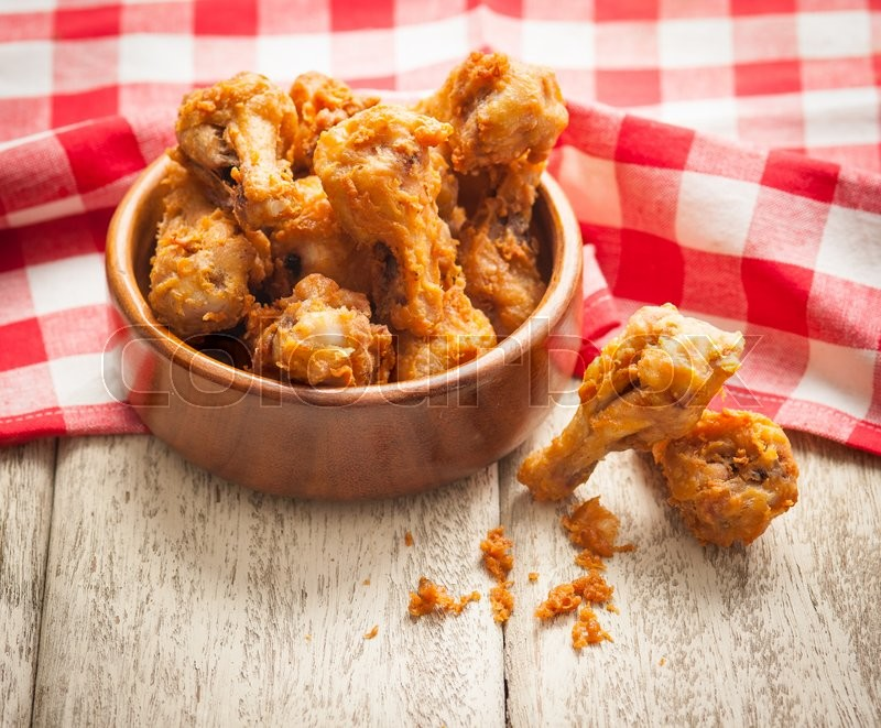 Stock image of 'Fried crispy chicken wings on a wood table'