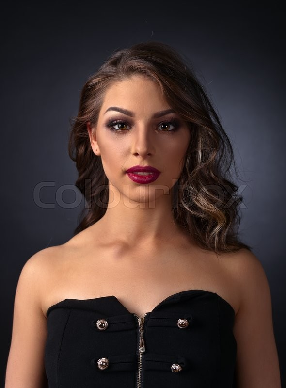 Stock image of 'Portrait of young beautiful woman on dark background'