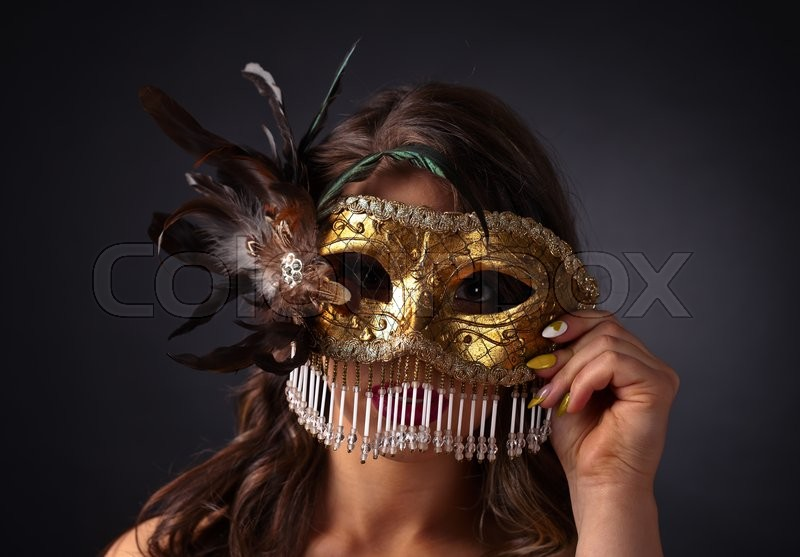 Stock image of 'Beautiful woman with gold carnival mask on dark background'