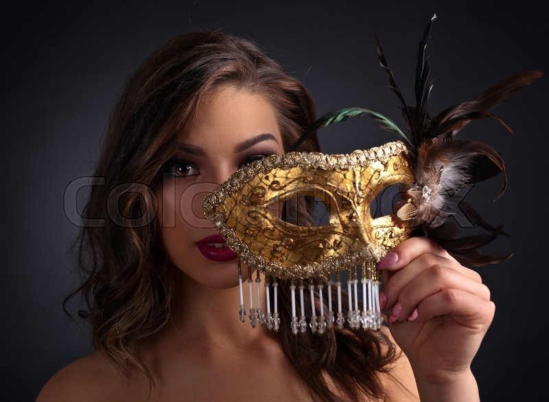 Stock image of 'Beautiful woman in black dress with carnival mask'