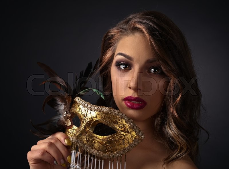 Stock image of 'Beautiful young woman with gold carnival mask'