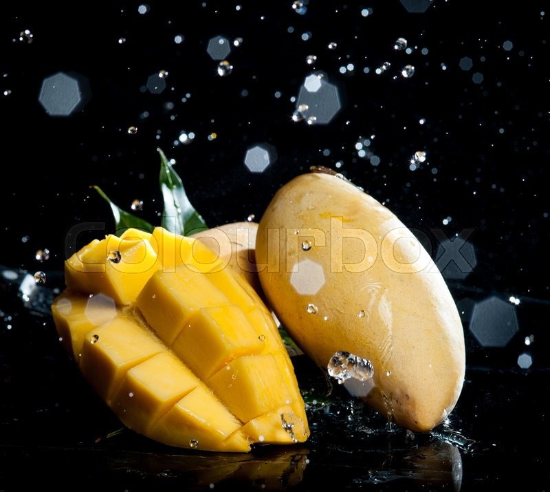 Stock image of 'Mango splashing over clear water on black background'