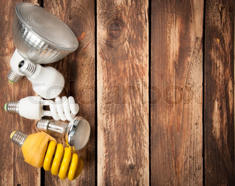 Stock image of 'Different lightbulbs on wooden background,top view'