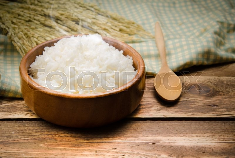 Stock image of 'Cooked rice and paddy rice on wood'