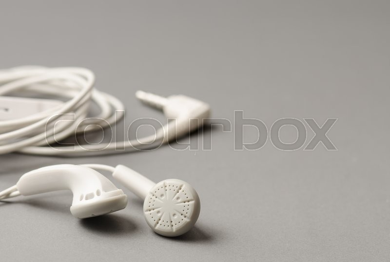 Stock image of 'White earphones on the gray background'
