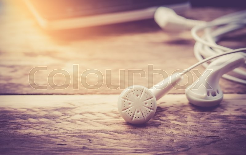 Stock image of 'Earphones and Mobile phone on wooden background,vintage color toned image'