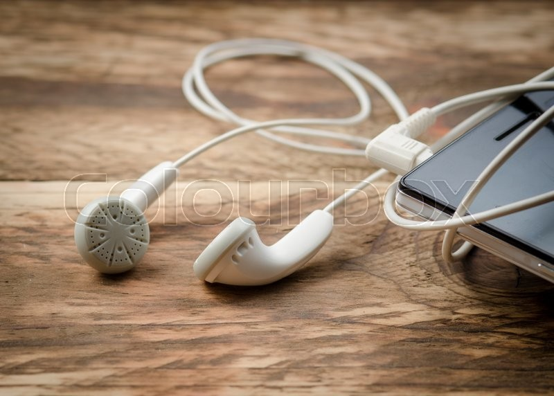Stock image of 'Earphones and Mobile phone on wooden background'
